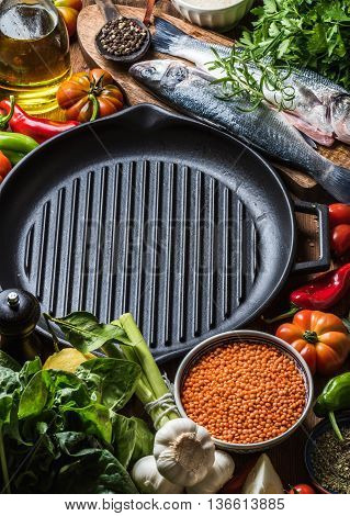Raw uncooked seabass fish with vegetables, grains, herbs and spices on chopping board, iron grilling pan in center with copy space, top view, selective focus