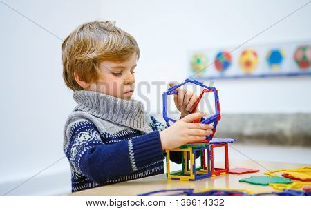 Little child playing with lots of colorful plastic blocks kit in maths museum. kid boy having fun with building and creating geometric figures.