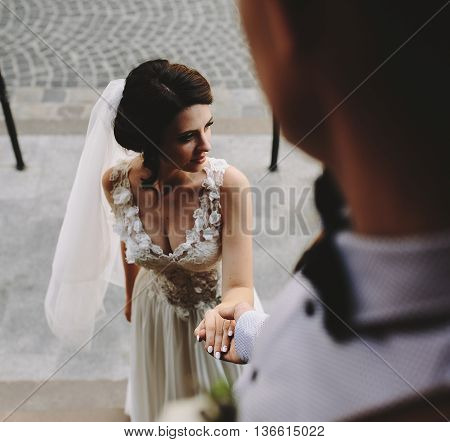 Groom holds the hand of the bride, close view