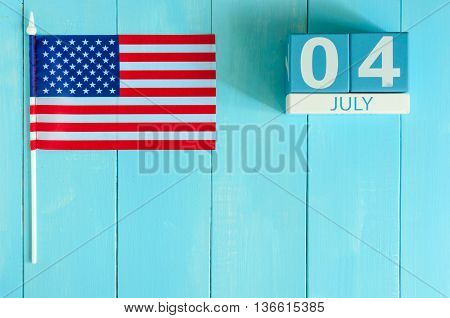 July 4th wooden color calendar with Stars and Stripes flag on blue background with flag of the USA. Summer day. Independence Day Of America.
