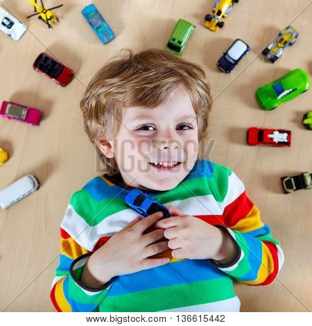 Lovely Little blond child playing with lots of toy cars indoor. Kid boy wearing colorful shirt. Happy preschool child having fun at home or nursery.