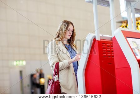 Tired young woman at international airport checking in on electronic terminal waiting for her flight. Upset passenger. Canceled flight due to pilot strike.