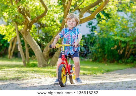funny blond kid boy in colorful clothes driving bicycle in domestic garden. Toddler child dreaming and having fun on warm summer day. Active games for children outdoors.