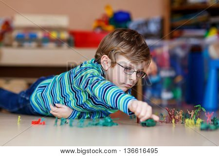 Cute blond child playing with lots of small toy soldiers, indoor. Active kid boy with glasses wearing colorful shirt and having fun at home or at nursery.