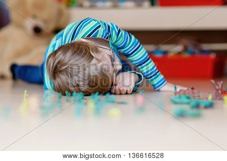 Little blond child playing with lots of small toy soldiers, indoor. Active kid boy with glasses wearing colorful shirt and having fun at home or at nursery.