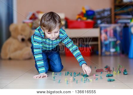 Little joyful blond child playing with lots of small toy soldiers, indoor. Active kid boy with glasses wearing colorful shirt and having fun at home or at nursery.