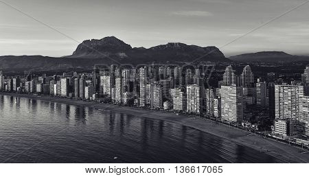 Aerial view of a Benidorm city coastline at sunset. Benidorm is a modern resort city one of the most popular travel destinations in Spain. Costa Blanca Alicante province. Black and white image
