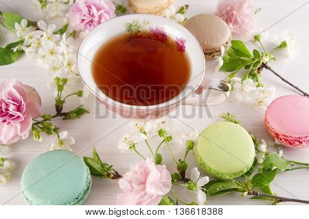 Tea with cherry blossom flowers macaroons. Spring concept