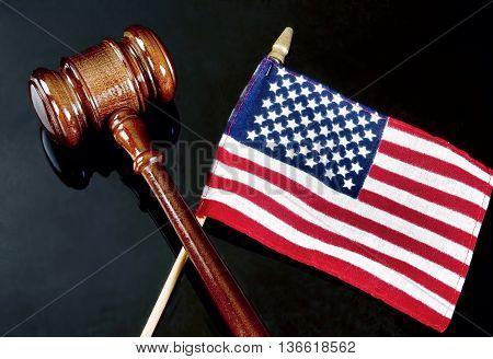 Gavel and American flag on dark background.