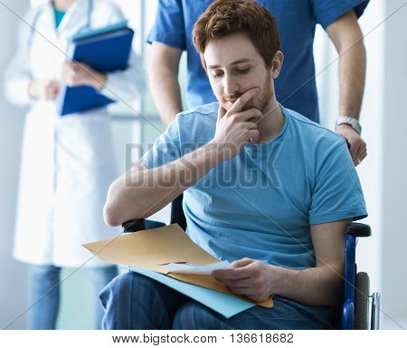 Disabled young man in wheelchair checking his medical records a male nurse is pushing him illness and healthcare concept