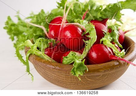 red radish in a wooden bowl on a white background