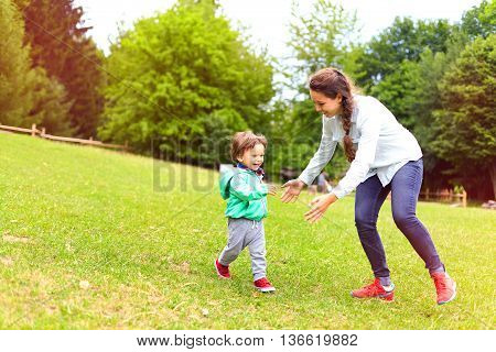 Mother Running With Son In The Park.