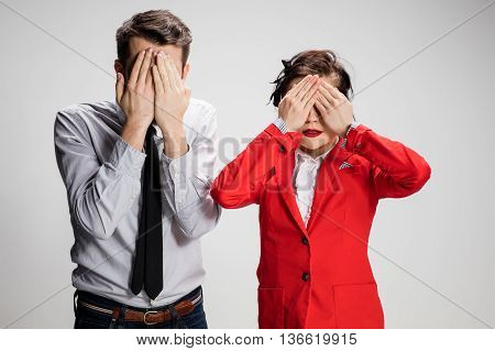 The business man and woman on a gray background closing eyes