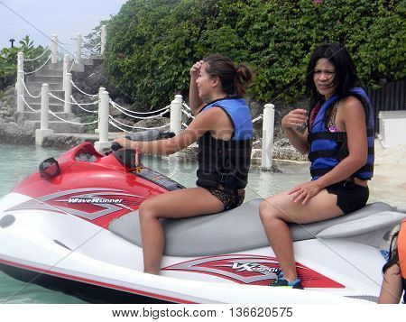 LAPU LAPU, CEBU / PHILIPPINES - JULY 28, 2011: Two women prepare for a ride in a jet ski at Shangri-La's Mactan Resort and Spa.