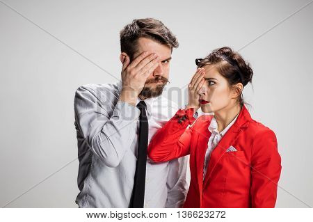 The business man and woman on a gray background closing one eye by hand