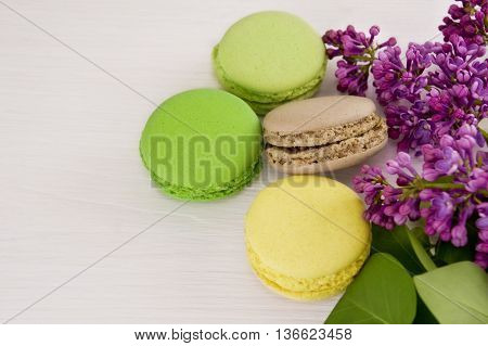 French macaroons with twigs of lilac. Close-up.