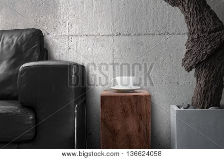 white coffee cup on wooden with black sofa and old root sculpture hard concrete wall in gray living room