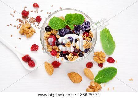 Healthy breakfast granola with yogurt nuts seeds and berries.