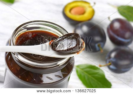 thick plum jam on plastic spoon and in a jar