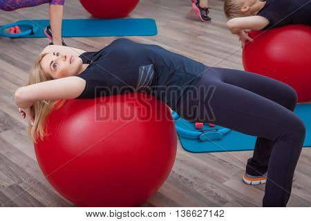Beautiful slim doing some gymnastics at the gym with fitball