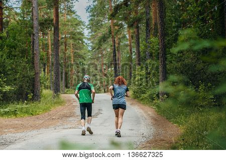 couple of athletes a man and woman running along road in forest during a marathon