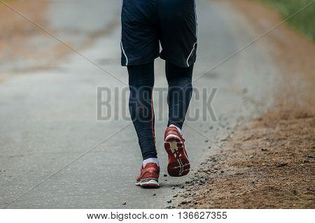 feet man running down road in woods during a marathon