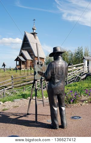 PLES, RUSSIA - SEPTEMBER 14, 2015: Monument to a paintor Isaak Levitan and a wooden church in Ples town, Russia. Mountain of Levitan. Popular touristic landmark.