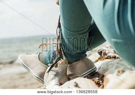 girl sitting on a log with his legs dangling