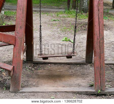 An old wooden swing in a lush backyard.