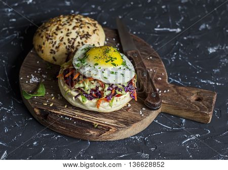 Homemade burger with fried egg and coleslaw on a rustic wooden board on a dark background. Healthy delicious food