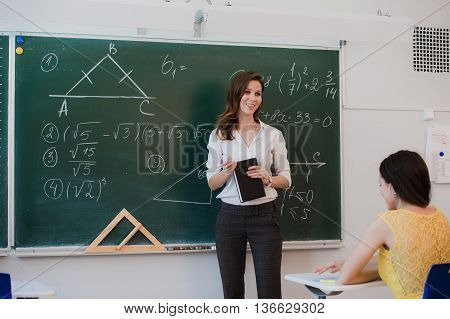 Young attractive female teacher interacting with her young primary school students asking a young girl for an answer.