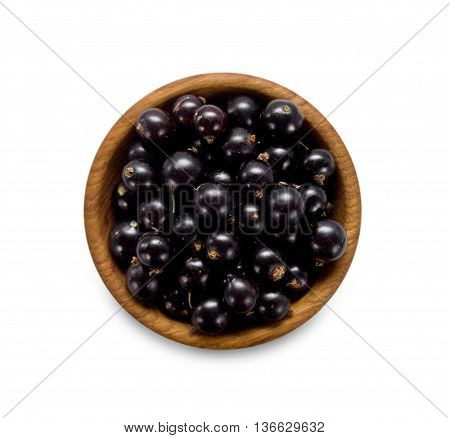 black currant in a wooden bowl. Top view. Ripe and tasty currant isolated on white background.