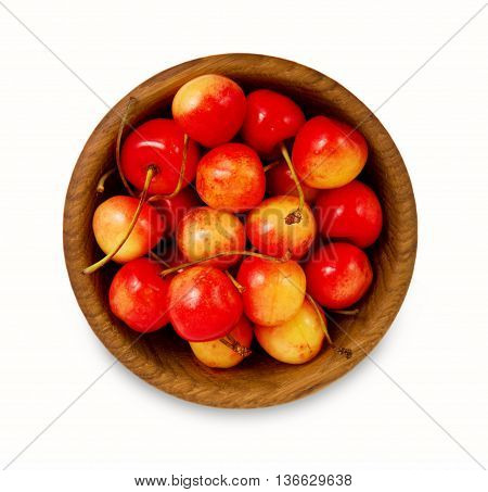 Red fresh cherry fruits in a wooden bowl. Top view. Ripe and tasty cherry isolated on white background.