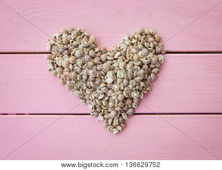 Sea shells in a heart shape on rustic wooden background