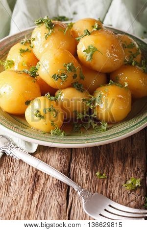 Glazed New Potatoes With Parsley Close-up On The Table. Vertical
