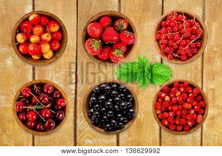Set various berries. Strawberries currant cherry. Collection of different fruits and berries isolated on white. Ripe and tasty berry on a wooden background
