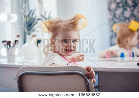 Little girl in front of the mirror doing her makeup