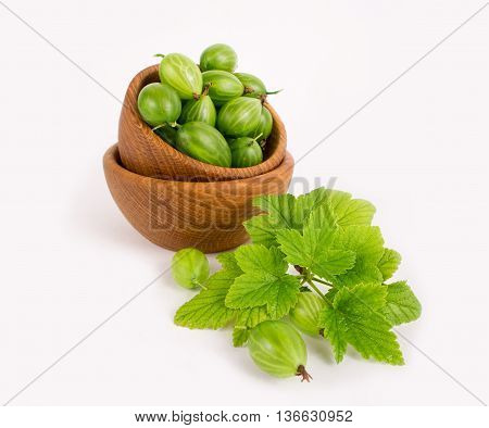 Gooseberry fruit. Ripe and tasty berry isolated on white background. Gooseberry in a wooden bowl.