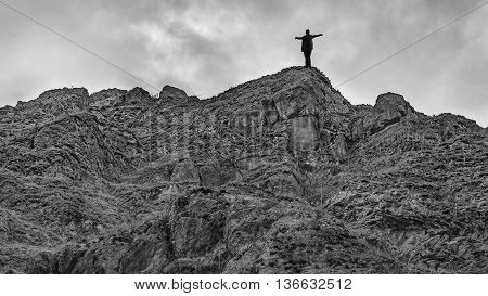 Man with open arms at the top of rocky mountain on a cloudy day.