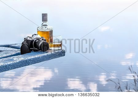 Bottle of tequila and tumbler with photo camera on the shore of lake