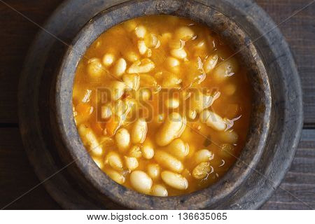 Cooked beans served in clay bowl on dark wooden background. Top view
