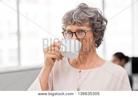 Senior businesswoman refreshing herself by drinking a cup of coffee. Close up face of mature business woman sipping a cup of coffee. Thoughtful senior woman enjoying tea.