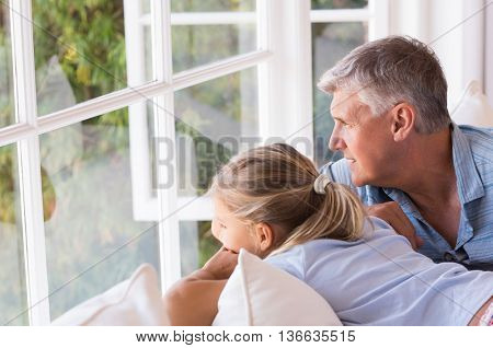 Young girl looking out of the window with grandfather. Senior man sitting with little girl near the window and looking outside. Grandfather and granddaughter thinking together.