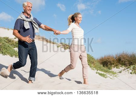 Happy senior couple running down the dune at beach. Smiling mature man and woman enjoying summer holiday together at beach. Romantic couple holding hands and jumping down the dune.