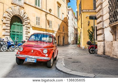 Rome Italy - May 2 2016. Red vintage Fiat Nuova 500 parked in the old street in Rome.