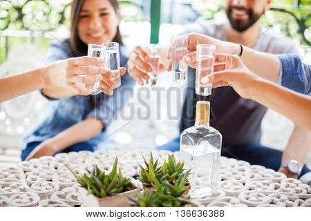 Closeup of a group of young Hispanic friends having fun together and drinking shots of tequila during a barbecue