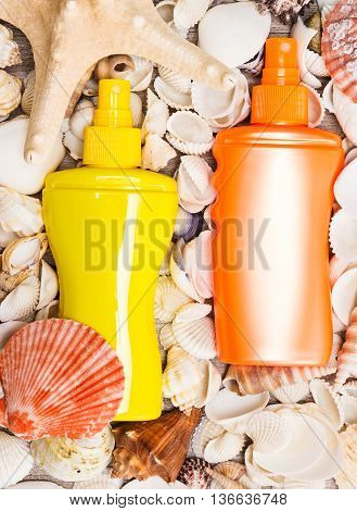 Yellow and orange containers of cosmetic sunscreen products with variety of shells and starfish. Concept of skin care cosmetics containing sun protection factor