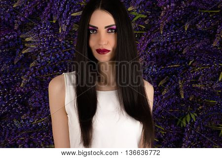 cute girl with long hair on a background of lupine flowers