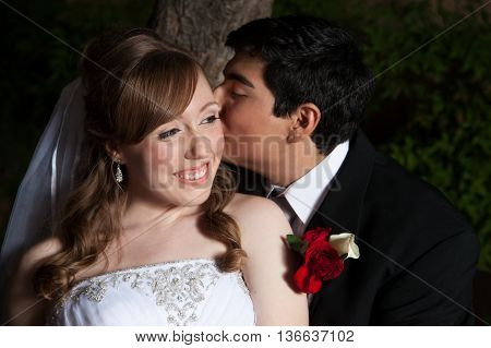 A Native American groom kisses his bride on the cheek on their wedding day. She is radiant.