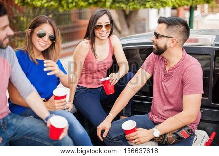 Group of attractive young friends drinking beer and hanging out in the back of pick up truck